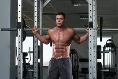 Jeune homme faisant la posture accroupie de Barbell d'exercice Photo libre de droits