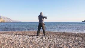 Jeune homme faisant la séance d'entraînement de sports dans le beau paysage de nature par la mer banque de vidéos