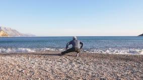 Jeune homme faisant la séance d'entraînement de sports dans le beau paysage de nature par la mer clips vidéos