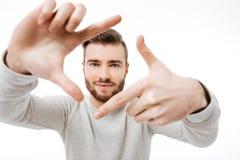 Jeune homme faisant le doigt encadrer en tant que directeur de la photographie et du smilibg au-dessus du fond blanc d'isolement images stock