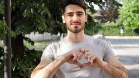 Jeune homme faisant le signe de coeur avec ses mains photos stock
