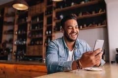 Jeune homme faisant un appel visuel au café Photo libre de droits