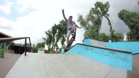 Jeune homme faisant un tour sur une planche à roulettes en parc de patin clips vidéos