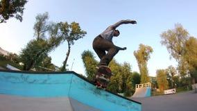Jeune homme faisant un tour sur une planche à roulettes en parc de patin banque de vidéos