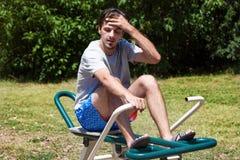 Jeune homme fatigué après l'exercice extérieur sur la machine à ramer photographie stock