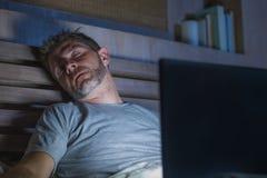 Jeune homme fatigué et épuisé d'intoxiqué d'Internet ou de travail dormant tandis que mise en réseau de fin de nuit avec l'ordina photo libre de droits