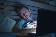 Jeune homme fatigué et épuisé d'intoxiqué d'Internet ou de travail dormant tandis que mise en réseau de fin de nuit avec l'ordina image stock