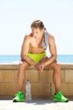Jeune homme fatigué sans la chemise se reposant après séance d'entraînement Image stock