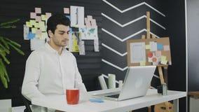 Jeune homme fatigué somnolent s'asseyant au bureau de bureau avec l'ordinateur portable banque de vidéos