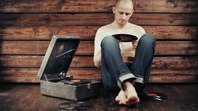 Jeune homme feignant pour écouter un vieux phonographe à la maison banque de vidéos
