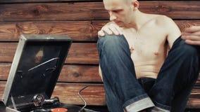 Jeune homme feignant pour écouter un vieux phonographe à la maison clips vidéos