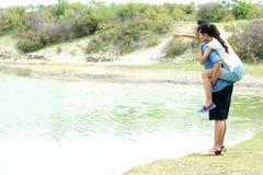 Jeune homme ferroutant son amie au bord de lac Photo libre de droits
