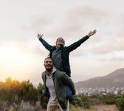 Jeune homme ferroutant son amie dans la campagne Images stock