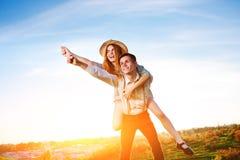 Jeune homme ferroutant son amie heureuse avec la main augmentée Rêver gai d'amants Images stock