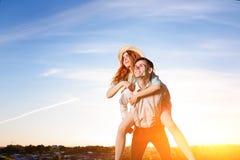 Jeune homme ferroutant son amie heureuse avec la main augmentée Rêver gai d'amants Photo libre de droits