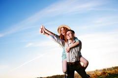 Jeune homme ferroutant son amie heureuse avec la main augmentée Rêver gai d'amants Image libre de droits