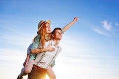 Jeune homme ferroutant son amie heureuse avec la main augmentée Rêver gai d'amants Images libres de droits