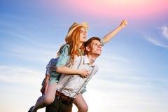 Jeune homme ferroutant son amie heureuse avec la main augmentée Rêver gai d'amants Photo stock