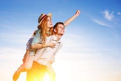 Jeune homme ferroutant son amie heureuse avec la main augmentée Rêver gai d'amants Photos stock