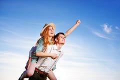 Jeune homme ferroutant son amie heureuse avec la main augmentée Rêver gai d'amants Photographie stock