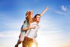 Jeune homme ferroutant son amie heureuse avec la main augmentée Rêver gai d'amants Image stock
