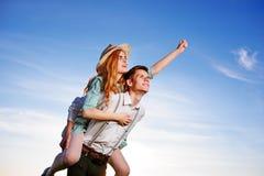 Jeune homme ferroutant son amie heureuse avec la main augmentée Rêver gai d'amants Photos libres de droits