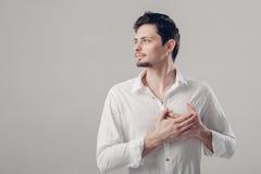 Jeune homme fier beau dans la chemise tenant la main sur le coffre sur le gris image stock