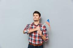 Jeune homme fier patriote tenant et tenant le drapeau des Etats-Unis Image libre de droits