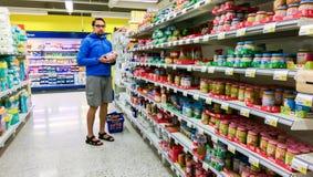 Jeune homme finlandais choisissant l'aliment pour bébé dans un S-marché de supermarché de suomi, à Tampere Image stock
