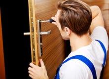 Jeune homme fixant la porte avec le tournevis Photo stock