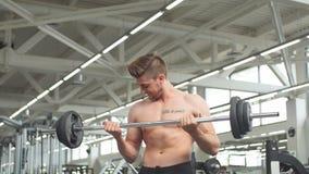 Jeune homme fléchissant des muscles avec le barbell dans le gymnase clips vidéos