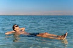 Jeune homme flottant sur la surface de l'eau de la mer morte photo stock