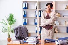 Jeune homme fou dans la camisole de force au bureau photos stock