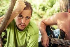 Jeune homme franc avec le sembler sincère chantant avec la guitare pendant la partie extérieure de camping parmi le feuillage Image stock