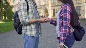 Jeune homme frottant la main de l'amie tendrement, amour d'étudiant, relations banque de vidéos