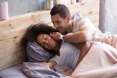 Jeune homme frottant les cheveux de son amie dans le lit Photo stock
