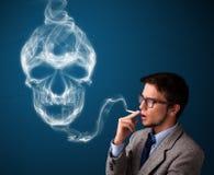 Jeune homme fumant la cigarette dangereuse avec de la fumée toxique de crâne Photo stock