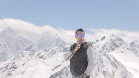 Jeune homme fumant une cigarette électronique sur un fond de belles montagnes banque de vidéos