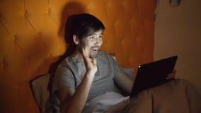 Jeune homme gai à l'aide de la tablette ayant la causerie visuelle en ligne avec l'amie tout en se trouvant dans le lit à la mais Photos stock