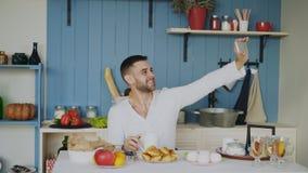 Jeune homme gai à l'aide du smartphone pour le portrait de selfie tandis que prenez le petit déjeuner pendant le matin photographie stock