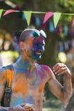 Jeune homme gai avec des verres dans la poudre bleue Images stock