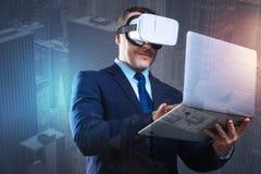 Jeune homme gai avec l'ordinateur portable essayant sur des lunettes de réalité virtuelle photographie stock
