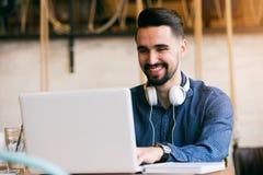 Jeune homme gai avec la barbe travaillant sur l'ordinateur portable dans le café image stock