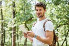 Jeune homme gai avec le sac à dos utilisant le comprimé dans la forêt photographie stock