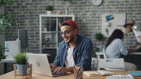 Jeune homme gai employant le travail de dactylographie d'ordinateur portable dans le bureau moderne de style de grenier banque de vidéos