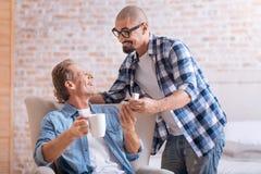 Jeune homme gai faisant la proposition à son associé âgé Image stock