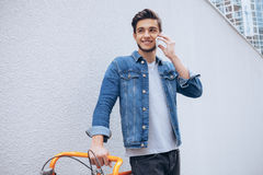 Jeune homme gai parlant au téléphone portable et souriant tout en se tenant près de sa bicyclette images libres de droits