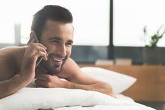 Jeune homme gai parlant par le téléphone portable dans la chambre à coucher Photo stock