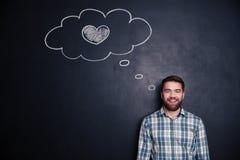 Jeune homme gai pensant à l'amour au-dessus du fond du tableau Photos libres de droits