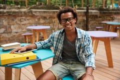 Jeune homme gai s'asseyant et souriant en café extérieur Image libre de droits
